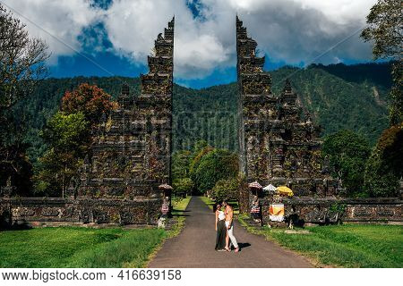 Traveling Couple In Bali. Happy Couple Vacationing In Asian Countries. Couple At The Bali Gate. A Ma