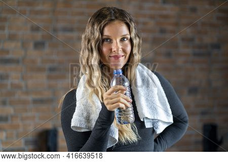 Woman With A Towel Holding A Bottle Of Water After Working Out At The Gym. Sporty Attractive Woman A