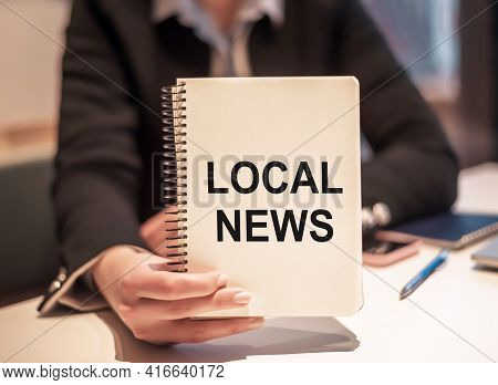 Business Woman Holds A Notebook With The Text Local News.