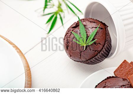 Weed Muffins In Baking Dish With Cannabis On Top, Cannabis Leaves, Hemp Branches On White Table. Mar