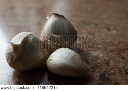 Three Garlic Cloves On A Brown Marble Countertop. Gastronomy.