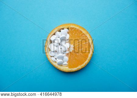 Fresh Orange Slice And White Pills On A Blue Background. Top View. The Concept Of Proper Nutrition A