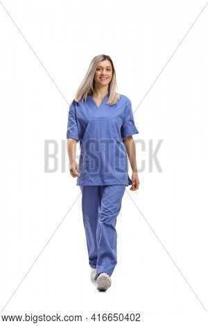 Full length portrait of a female health care worker in a blue uniform walking towards camera isolated on white background