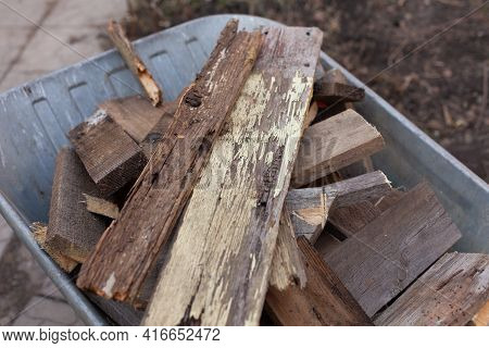 Old Wooden Planks Laying In A Wheelbarrow. Close Up.