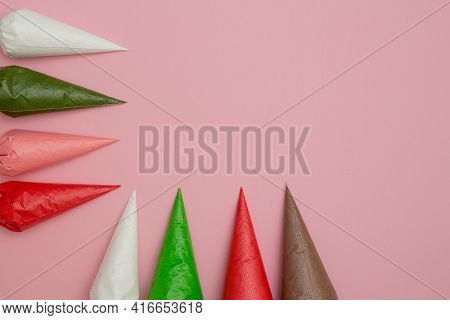 Multicolored Glazing In Icing Bags And Star Shaped Sprinkles On The Pink Table. Set For Decorating D