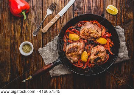 Chicken Thighs Baked With Red Bell Peppers, Rosemary And Lemon In Cast Iron Skillet. View From Above