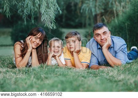 Beautiful Happy Caucasian Family Of Four People Lying On A Ground In Park On Summer Day. Mother And