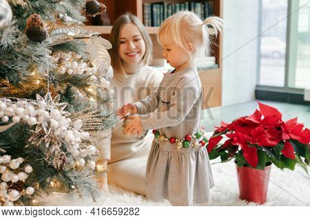 Happy Caucasian Mother With Baby Girl Decorating Christmas Tree With Ornaments Baubles Toy. Happy Fa