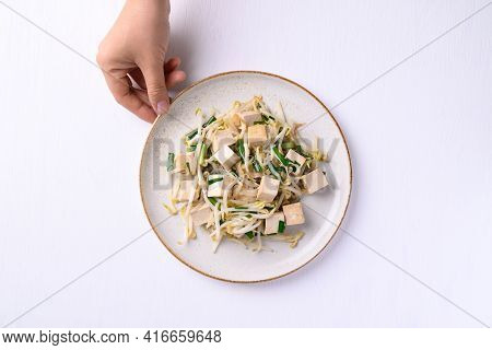 Stir Fried Tofu With Mung Bean Sprouts On Dish Holding By Hand On White Background, Asian Healthy Ve