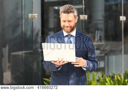 Business People. Urban Professional Business Man Using Laptop Smiling Happy Outside Office Building.