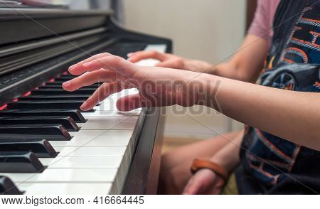 Piano Private Lesson. Master Teaches A Child To Play Piano. Young Woman Is Teaching A Kid To Play Th