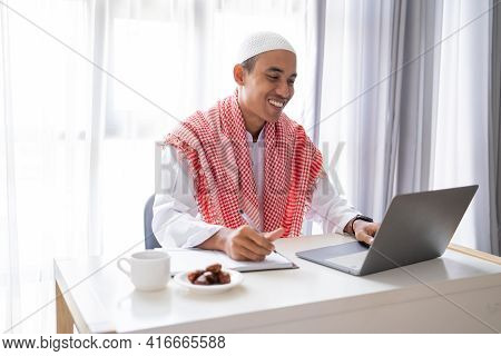 Muslim Businessman Working Using Laptop While Sitting On The Desk