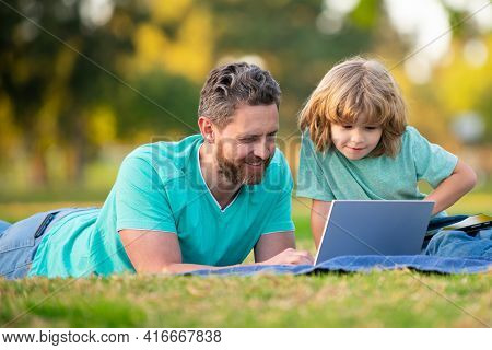 Father And Son Online Learning. Concept Of Friendly Family. Kid With A Laptop Outdoors In The Summer