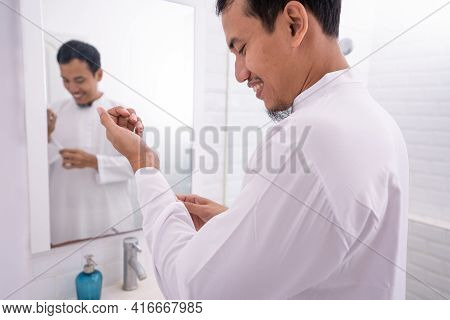 Muslim Man Looking At Mirror And Get Dressed Before Going To The Mosque