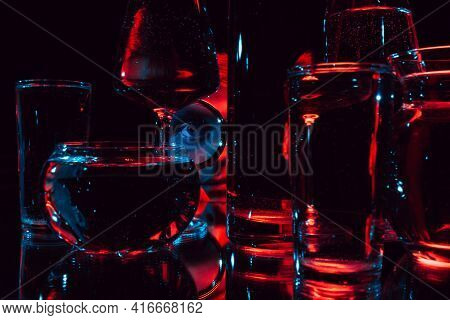 Portrait Of A Strange Man Looking Through A Magnifying Glass And Glass Glasses With Water