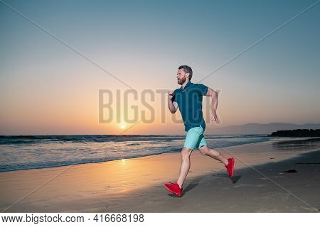 Portrait Of Active Middle Age Man Jogging Running Outside By Sea