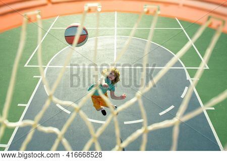 Child Shooting Basketball Ball And Playing Basketball, Lower View Wide Angle. Basketball Kids Traini