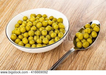 White Glass Bowl With Canned Green Peas, Metallic Spoon With Green Peas On Brown Wooden Table