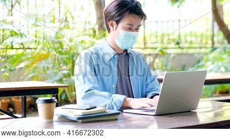 Young Asian Campus Student Man Wearing Protection Mask Working With Laptop Computer While Online Stu