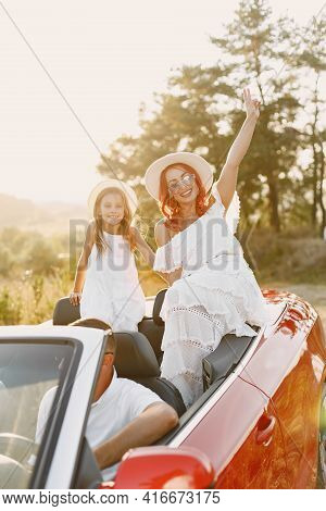 Family In A Cabriolet Convertible Car At The Sunset
