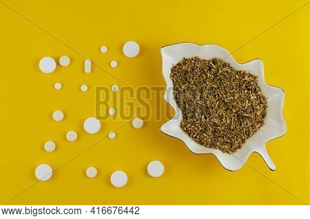 White Decorative Plate With Medicinal Herbs And Pills On Yellow Background. Ceramic Plate In The For