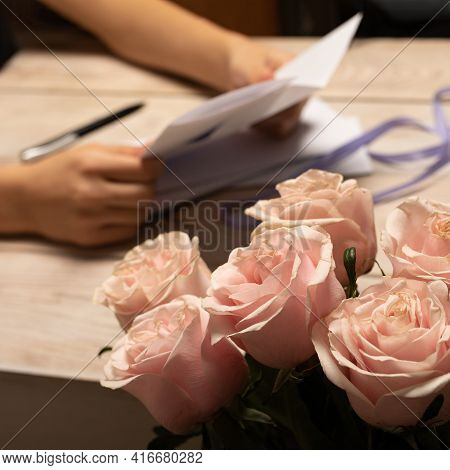 Flowers Of Bouquet Of Several Soft Pink Roses Close-up On Blurry Background Of Hands Holding An Open
