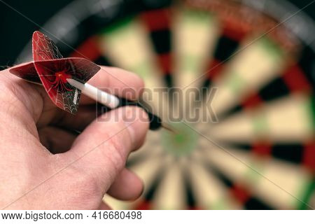 Man Hand Is Holding Dart And Aiming At Target. Achieving Goal. Game Of Darts. Aspiration, Determinat