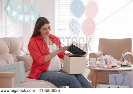 Happy Pregnant Woman With Gift Box In Room Decorated For Baby Shower Party
