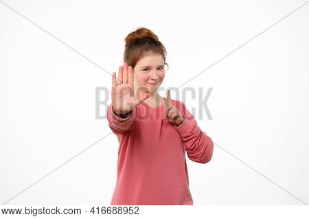 Young Girl In Pink Casual Sweatshirt Shows Stop Sign, Keeps Palm Forward To Camera With Strict Expre