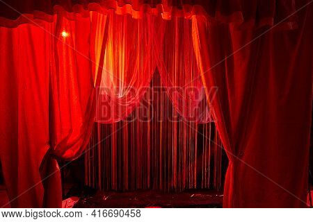 A Red Curtain Similar To A Theater Or Circus Curtain In A Studio. Background In The Photo Studio For
