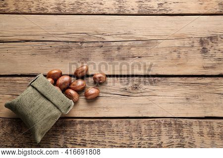 Overturned Sackcloth Bag With Jackfruit Seeds On Wooden Table, Flat Lay. Space For Text