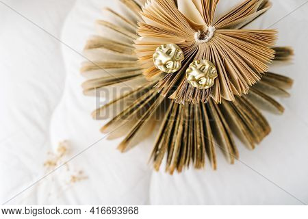 Womans Jewellery. Golden Earrings On Book Pages.