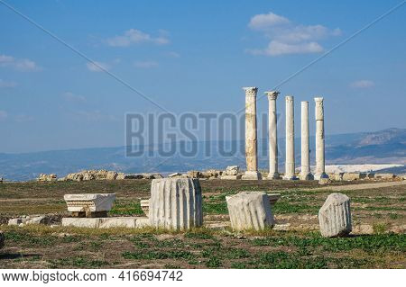 Remains Of Ancient Columns & Its Pylons With Ornaments. Colonnaded Street Is On Background. Shot In