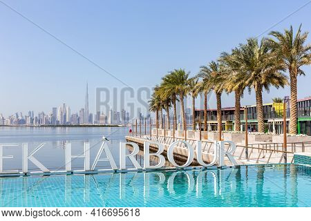 Dubai, Uae, 22.02.2021. Dubai Creek Harbour Sign By Turquoise Water Pool With Rows Of Palm Trees And