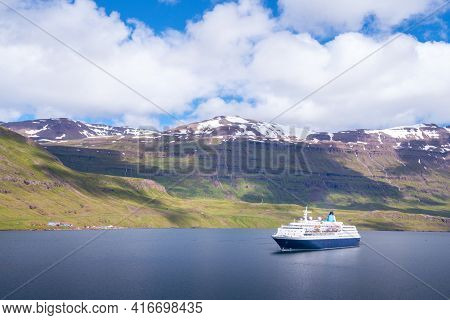 Blue And White Cruising Ship In A Fjord Of Seydisfjordur, Iceland, On A Warm, Partly Cloudy Day.