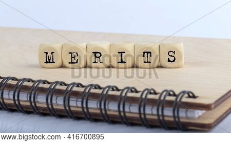 Word Merits Made With Letters On The Wooden Blocks On Wooden Notepad