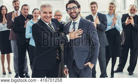 Boss And Business Team Congratulating The Best Employee At The Meeting.