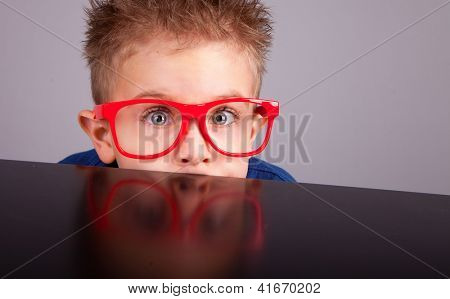 Five years old little cute boy hiding behind a table poster