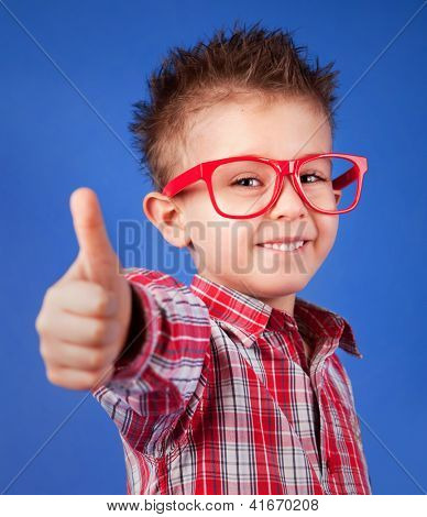 Cheerful five years old boy with thumb up