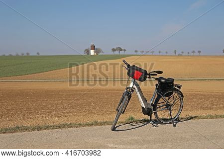 The E-bike Stands Near A Plowed Field