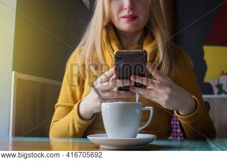 Blogger Girl Sits In A Cafe And Shoots A Cappuccino Foam On The Smartphone. Work In Social Networks,