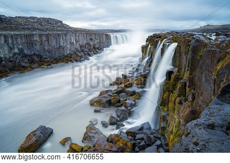 Long Exposure Of Selfoss Waterfall In Iceland On A Cloudy, Rainy Day. Wild River Runs Between Steep