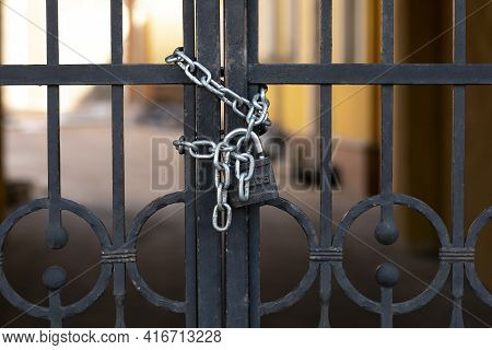 Black Iron Gate With Rust Closed On Padlock With Chains, Perimeter Security