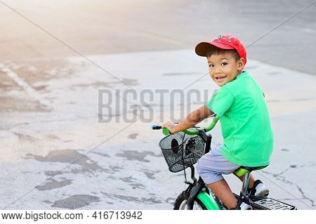 Portrait Image Of 4-5 Years Old Kid. Happy Asian Child Boy Riding A Bike Or Bicycle On The Road. He