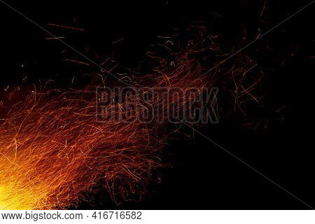 Trails Of Sparks From Bonfire Against Night Sky