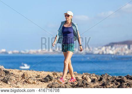 Young Slim Woman Enjoying Walking Along Coastline