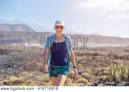 Smiling Woman Walking On The Path In Volcanic Area