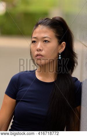 Portrait Of Beautiful Rebel Asian Woman Thinking Outdoors
