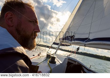 Silhouette Of Adult Bearded Man Portrait In Sunset Light Sailing On A Sailboat During Sailing. Summe