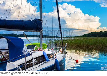 White And Blue Sailing Boat Moored On A Lake With Reeds On A Background With White Clouds And Blue S
